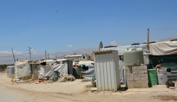 Links de wc, rechts de watertank van een klein vluchtelingenkampje