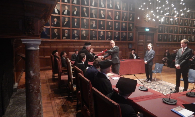 Dr. Jan van Lopik receives his doctorate diploma from his promotor at Utrecht University, Professor Ruud Schotting
